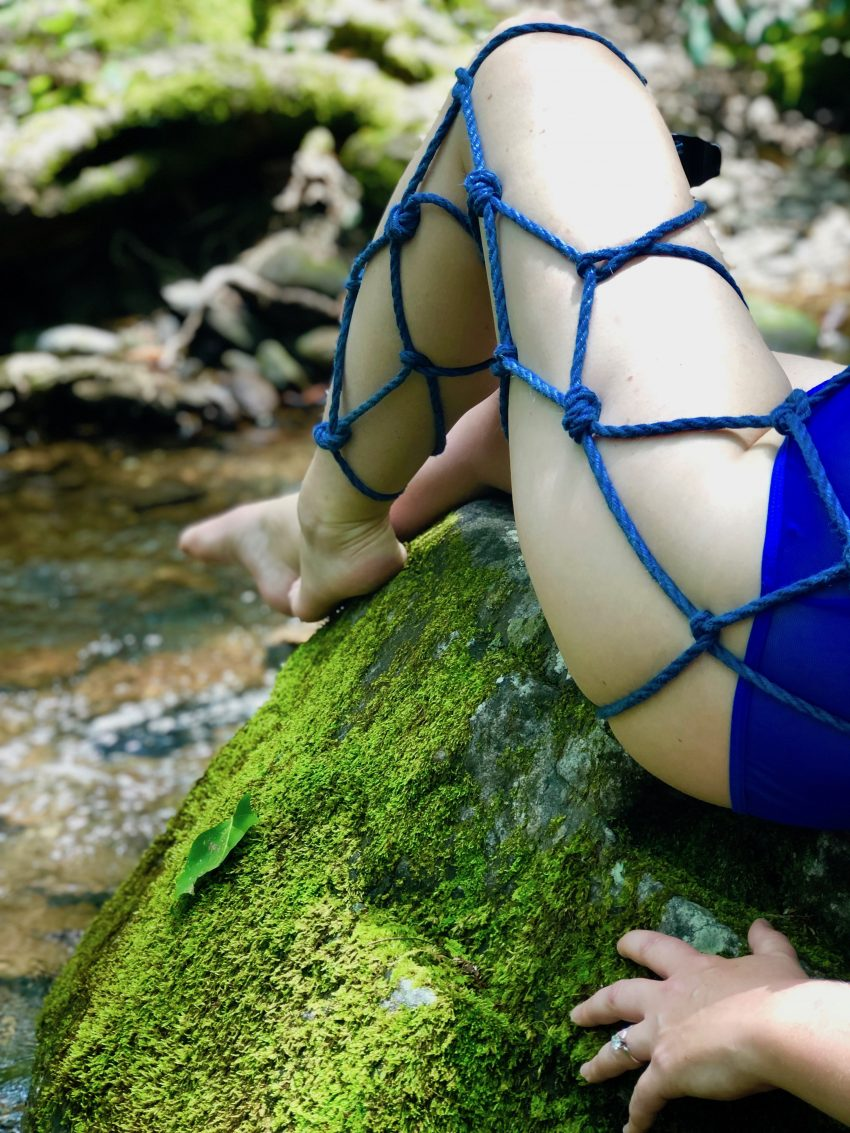 blue's thigh is wrapped in a net of rope and she is sitting on a moss covered rock in a stream.