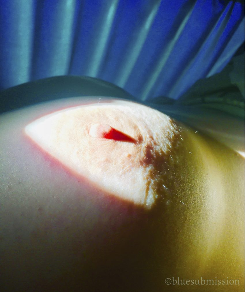 A closeup of Q's breast and nipple, highlighted in a triangle of light.